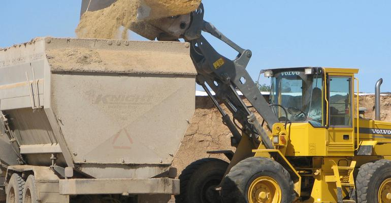 Digger truck shoveling feed into truck cargo bed