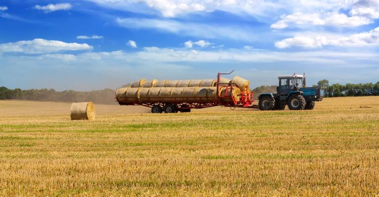 A tractor carrying hay bales in a field