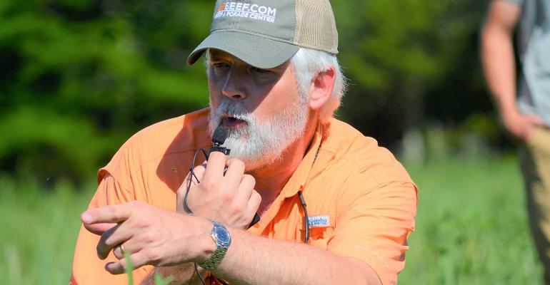Pat Keyser kneels in pasture of native grasses