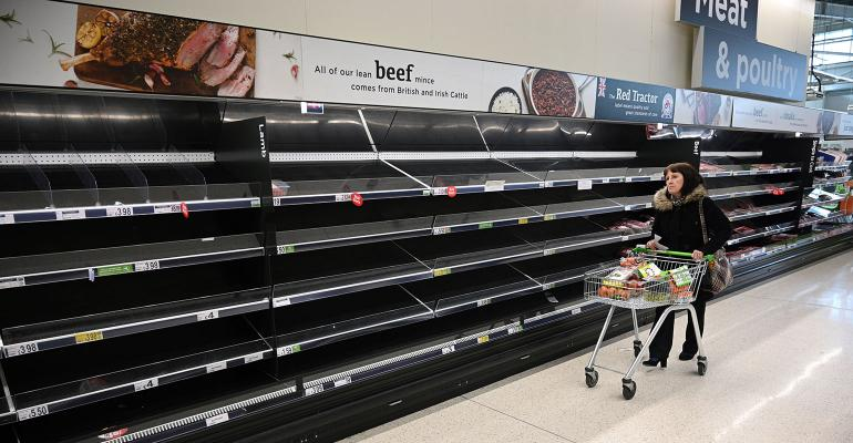 A shopper walks past empty food shelves amidst the novel coronavirus COVID-19 pandemic, in Manchester, northern England on March 20, 2020.