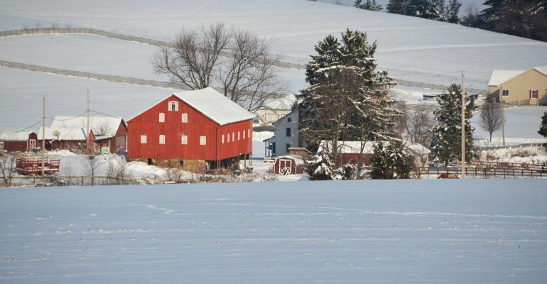A red barn shows brightly against a winter landscape