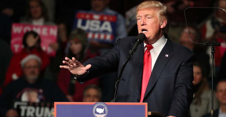 Donald Trump gestures while at podium.