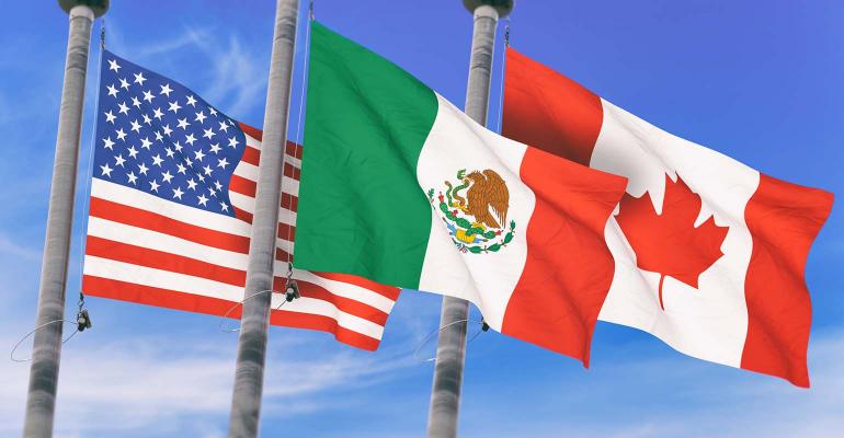 Canada, Mexico and US Flags over blue sky,