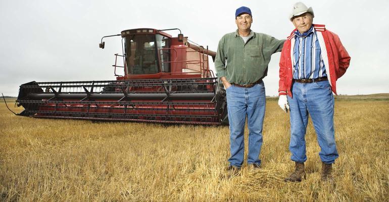 Two men standing in field away from combine.