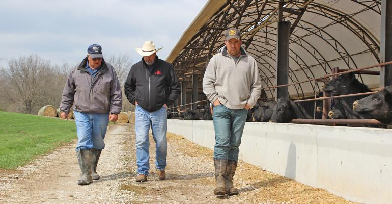 3 men walking by hoop barn