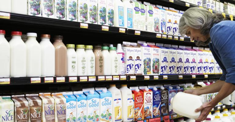 Milk on shelf with female consumer checking label