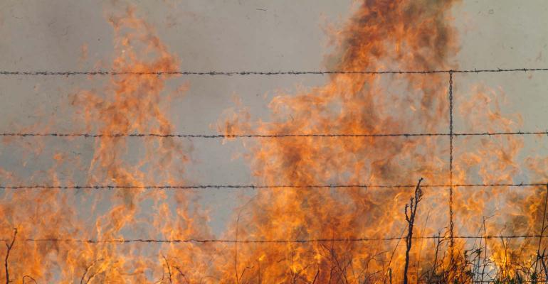 Burning Prairie Grass behind barbed wire fence.