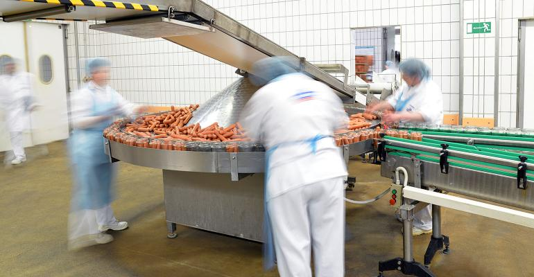 food industry workplace - butchery factory for the production of sausages - women working on the assembly line