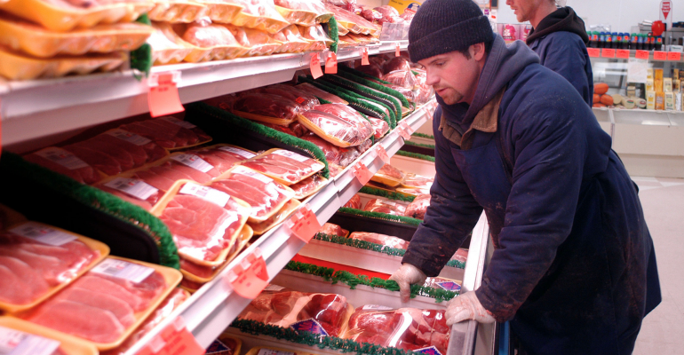 A employee stacks a beef shelf