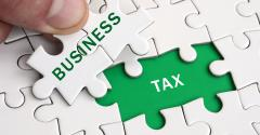 A human hand fills in the business pieces of a tax jigsaw puzzle