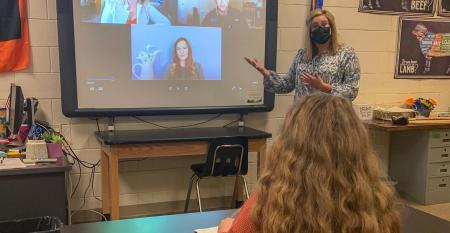 A teacher wearing a face mask and showing a Farm Progress Virtual Experience session with students in a classroom