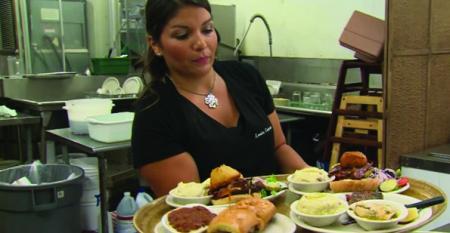 Waitress wrangling a heap o' steaks