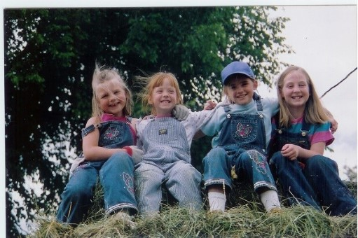 My cousin Mikayla, sister Laura, cousin Kristin, and I baling hay on a warm summer day