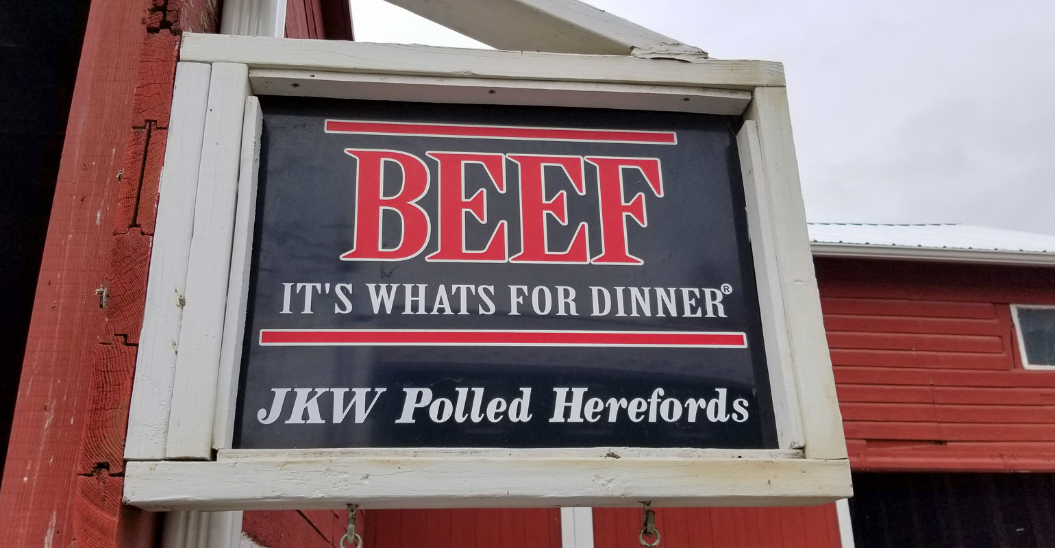 An outdoor sign at JKW Polled Herefords reads 'Beef, it's what's for dinner'